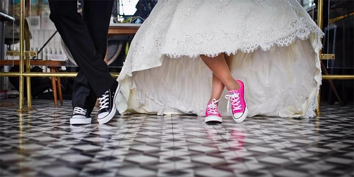 bride and groom in sneakers green wedding