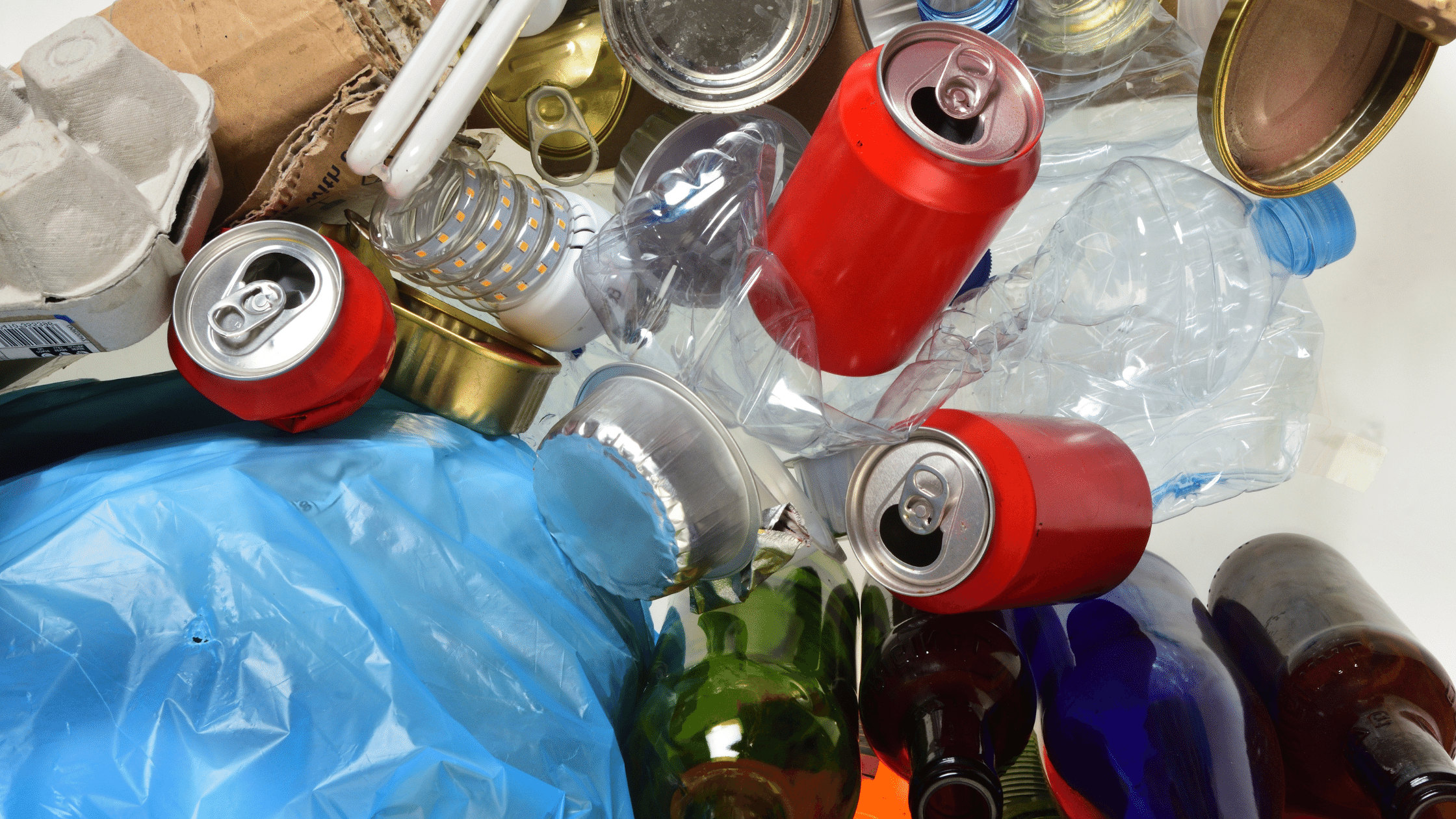 image showing pile of mixed recyclables blue plastic bag, cans, plastic bottles, lightbulb, glass bottles, etc