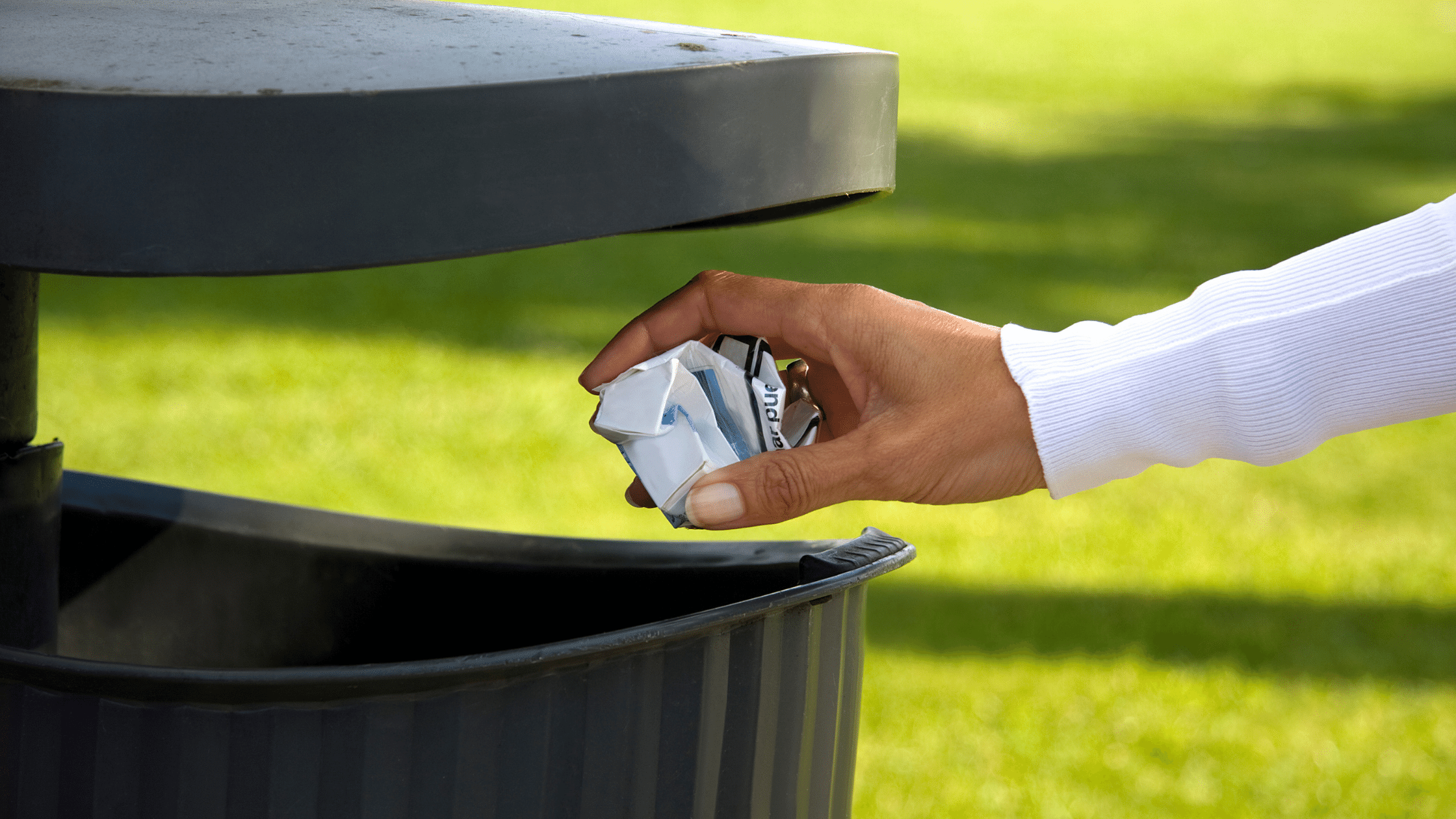 image showing a waste bin and a hand about to throw a ball of paper into the bin opening