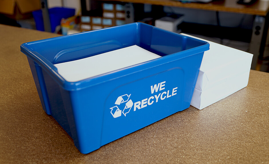 Busch Systems Deskside Recycler container in blue with mobius loop we recycle graphic filled with paper