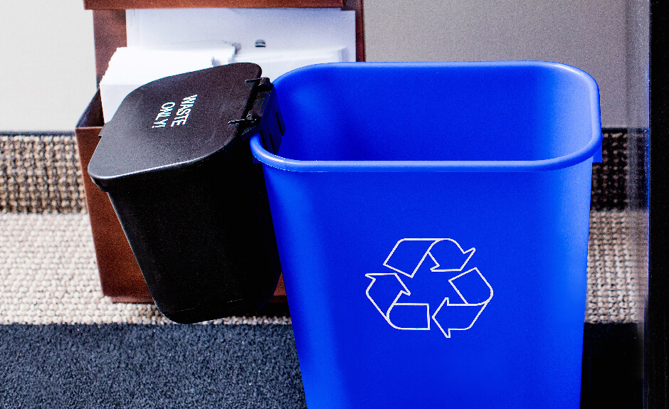 Busch Systems black hanging waste basket attached to blue recycling container with mobius loop graphic