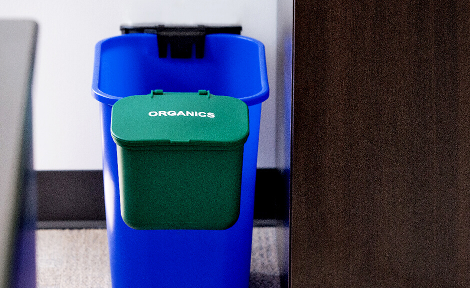 Busch Systems green organics hanging waste basket attached to blue recycling container