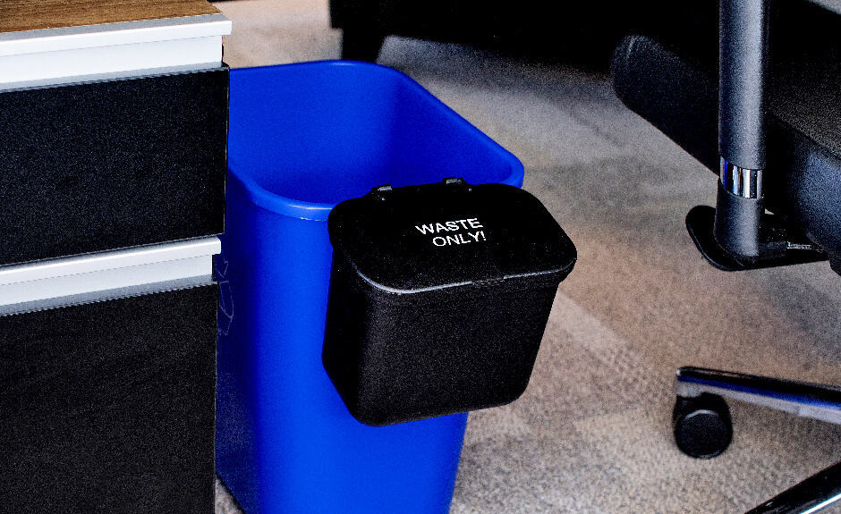 Busch Systems black hanging waste basket attached to blue recycling container